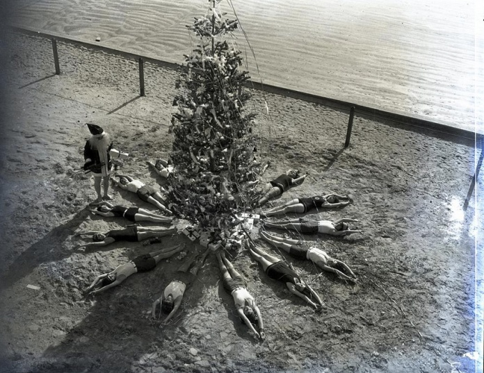 Santa Claus on beach with swimmers splayed around Christmas tree, 1927. From NMAH Archives